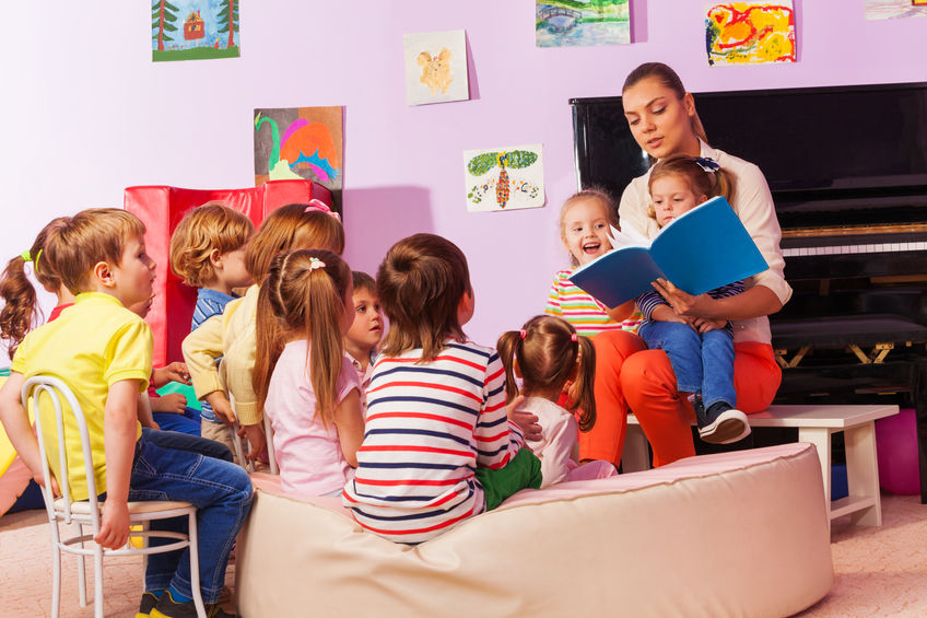 preschool kids sitting in group listening to teacher read