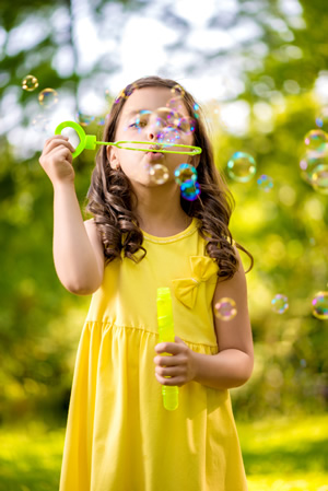 Girl in Yellow Dress Blowing Bubbles