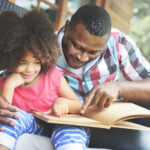 Father and daughter reading book