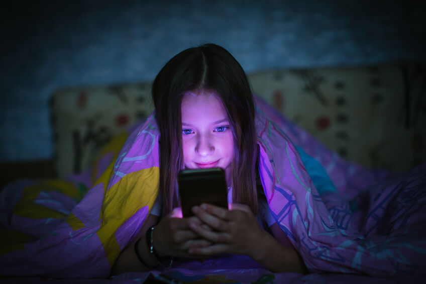 little girl in bed staring at smartphone